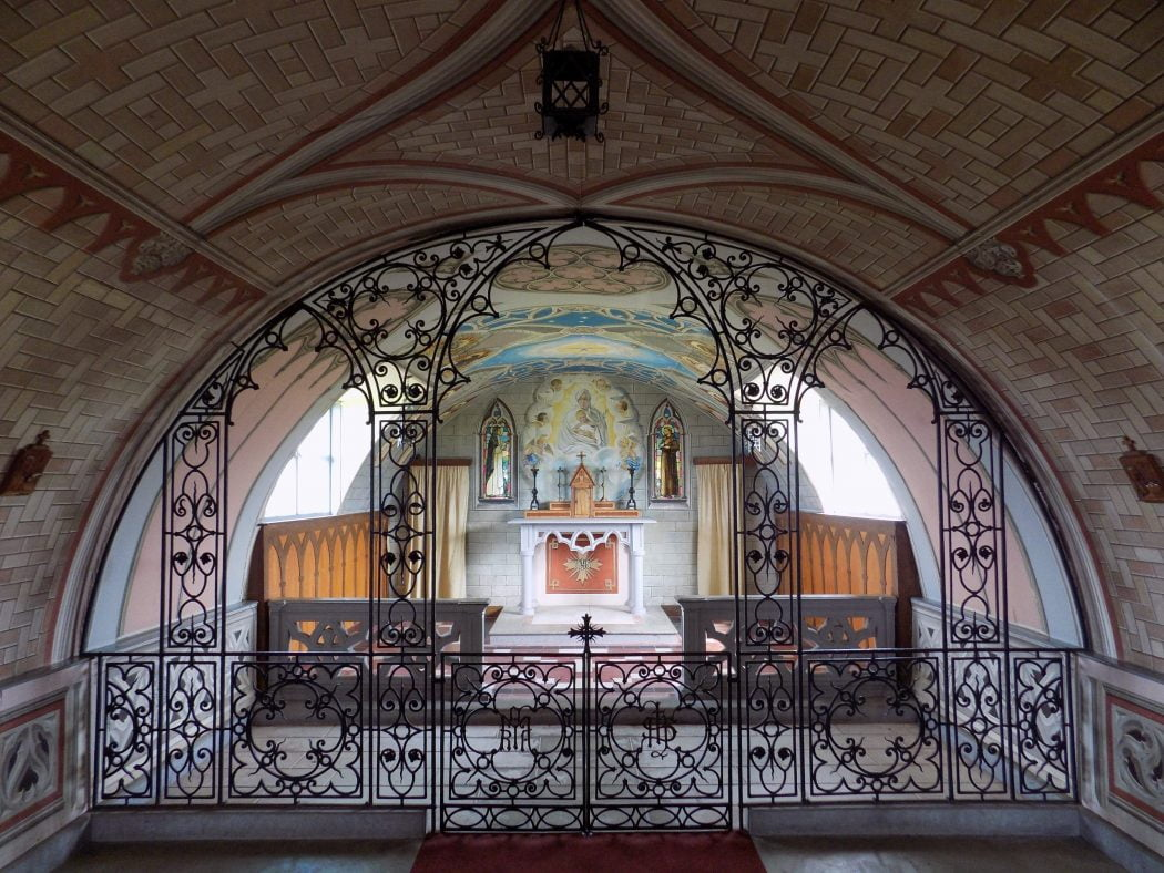 Picture of the interior of the italian chapel on Orkney - Three Day Tour. This is a converted Nissan Hut, but painted beautifully on the inside to look like a chapel in Italy. Centre back there is a painting of the Madonna and child, and in the foreground there is much decorative ironworks and gate.