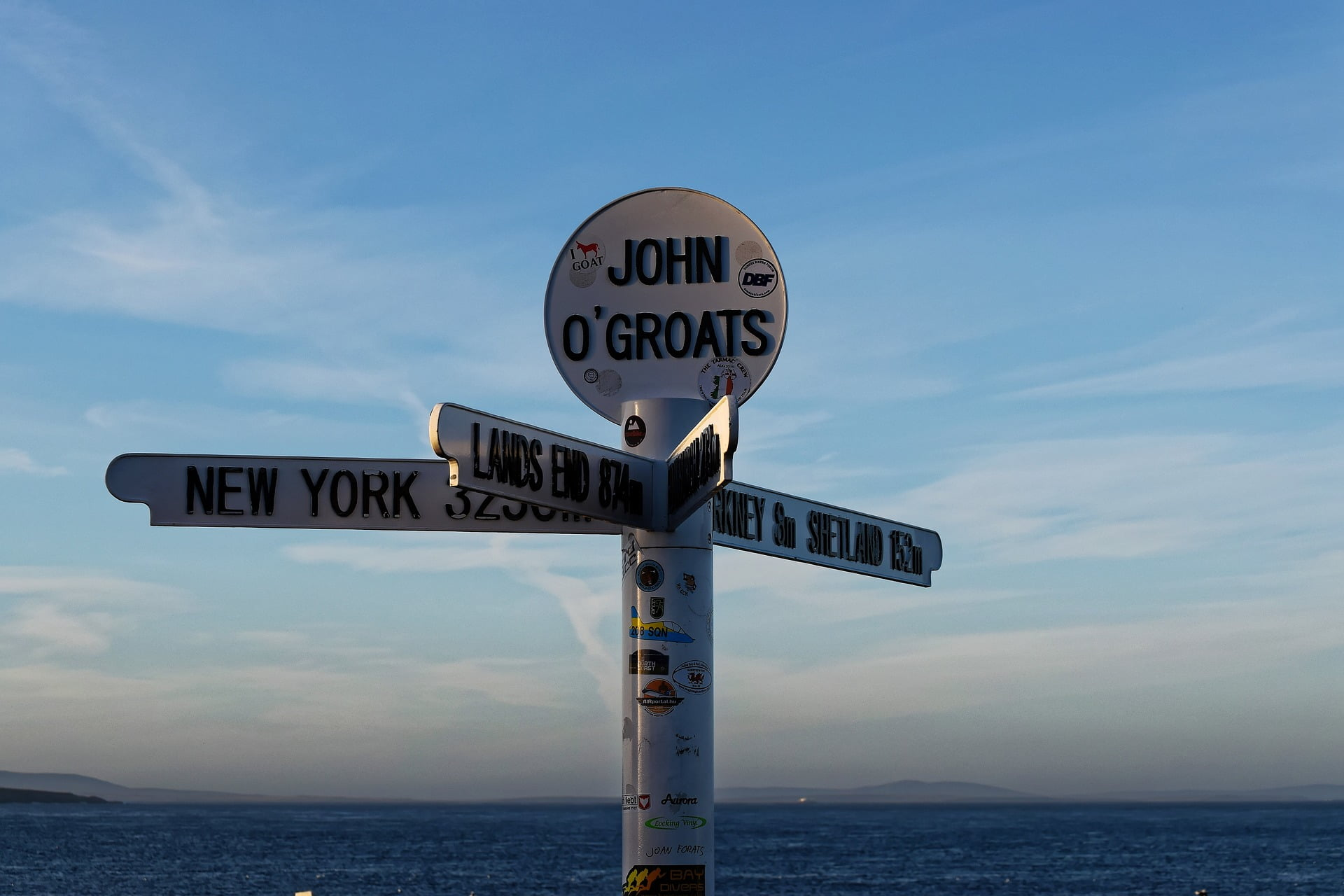 Our NC500 the North East day Tour takes you to the John O' Groats sign, which is the subject of this shot. A little of the sea is showing, dark blue, at the bottom of the picture. Two headlands show, distant and low, to the left hand side, and some islands on the far horizon on the right hand side. The sky is blue. The obvious subject, dominating the picture, is the close up view of the sign. It is a white pole, covered in visitors stickers, surmounted by a disc with the words John O Groats. It has four visible fingersigns pointing out from it, pointing to New York, Lands End, Orkney and Shetland and giving mileages (not all of which are visible).