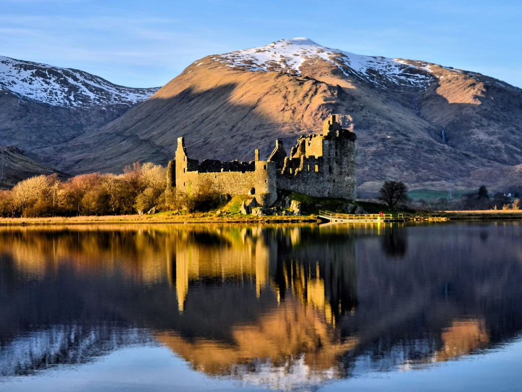 There is a blue sky with two snow capped mountains. The foreground is a lake, and the centrepiece is a ruined castle projecting into the lake on a wooded spit of land. This whole picture is then imperfectly reflected in the rippled surface of the lake.