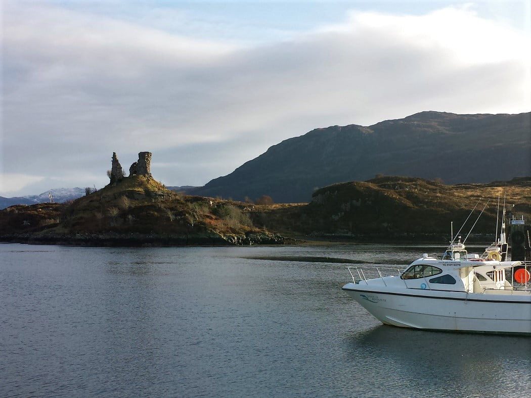 Castle Maol, a very ruined Viking castle stands on a rocky knoll across about 200 metres of calm sea. A white cabin cruiser rests at anchor in front right. The sky is overcast and there are low snow-speckled mountains in the background.