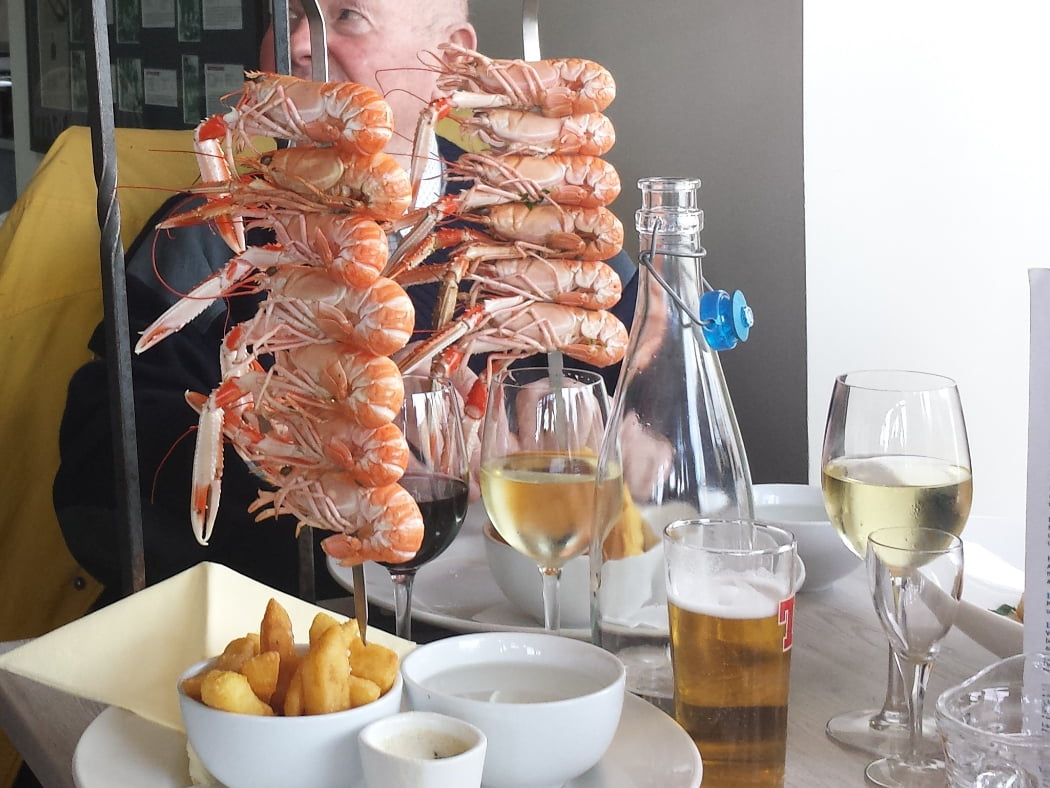 Tall standing skewers on a restaurant table, on our Ardvreck Castle and Geopark Tour. Each skewer holds up to 7 langoustine. Wines, a lager and a bowl of chips also adorn the table.