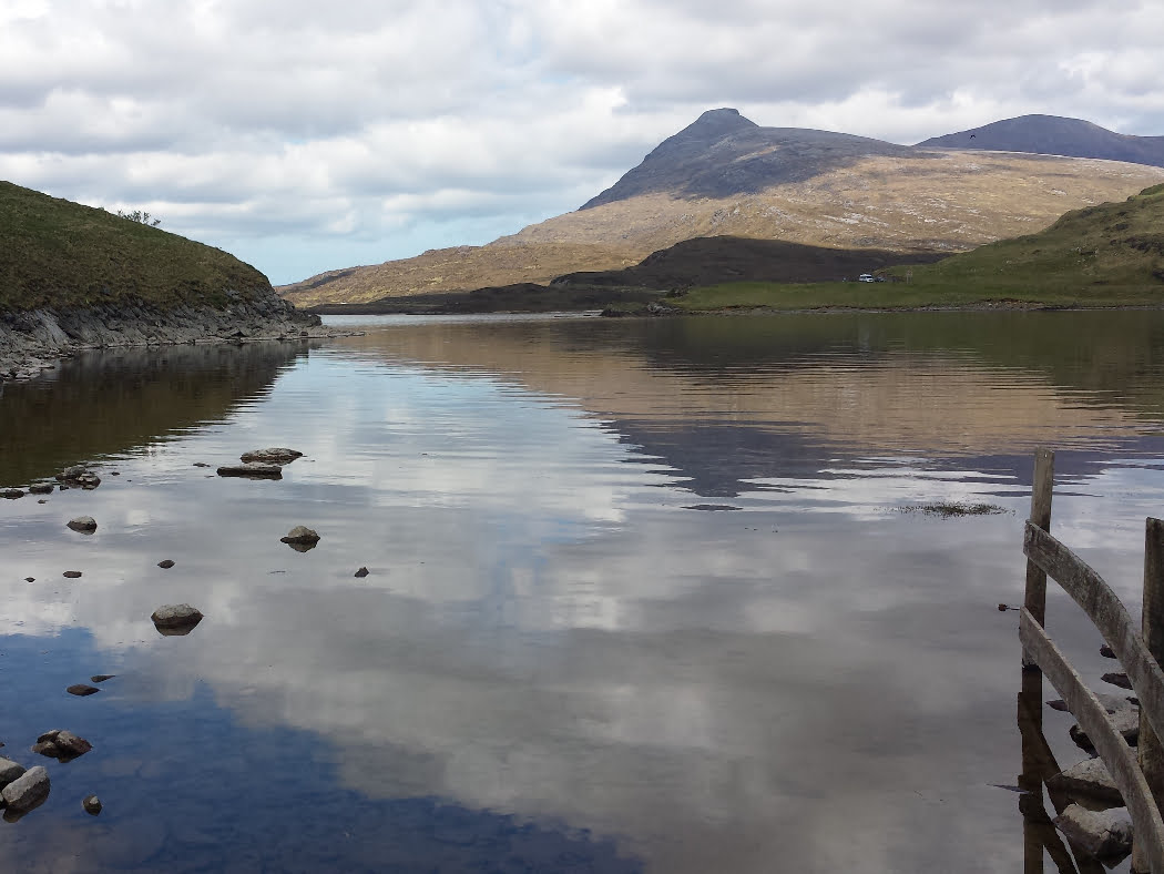 A still lake along our Ardvreck Castle and Geopark Tour. The water is so clear that the bottom is visible. A fence protrudes into the water from the right. A double headed mountain is visible across the lake, under a cloudy sky.