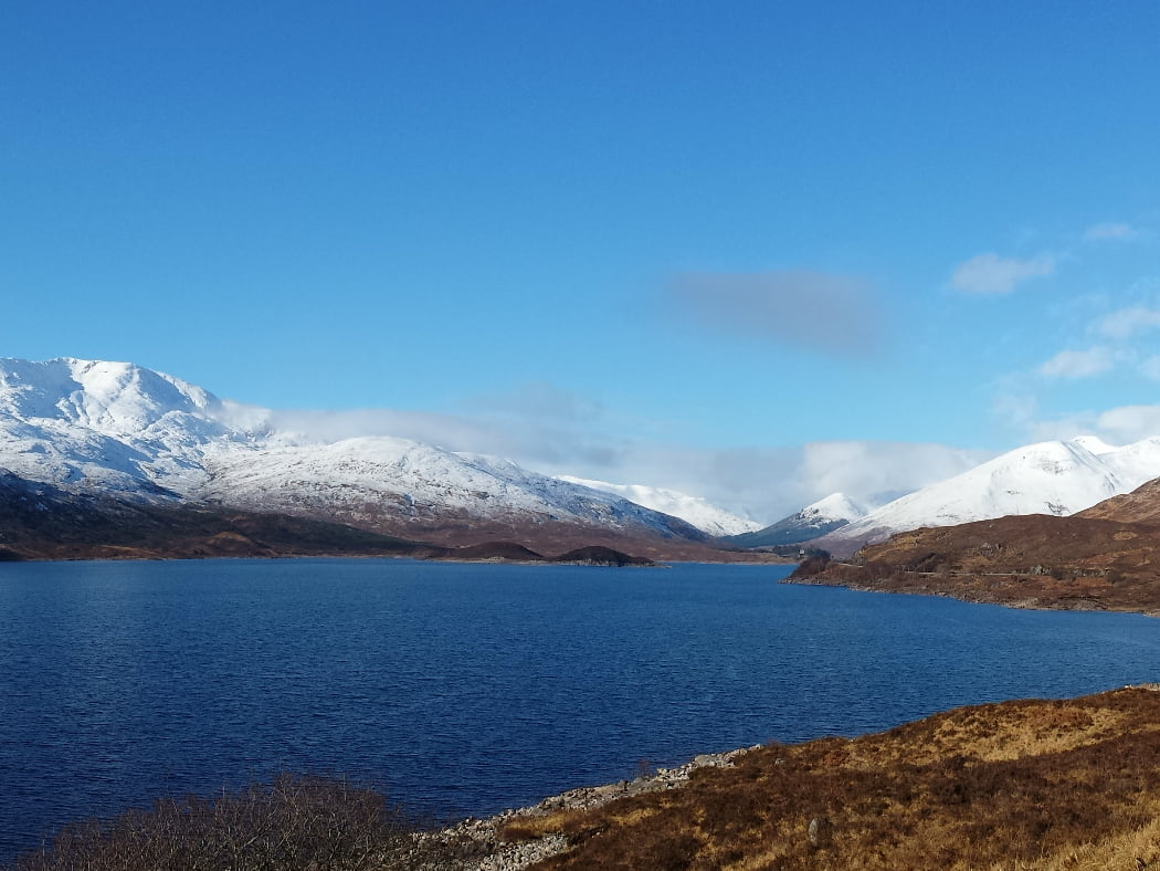 Light blue sky and a dark blue lake which we drive alongside on the Eilean Donan Castle Tour. There are impressive snow clad peaks on both sides of the lake.