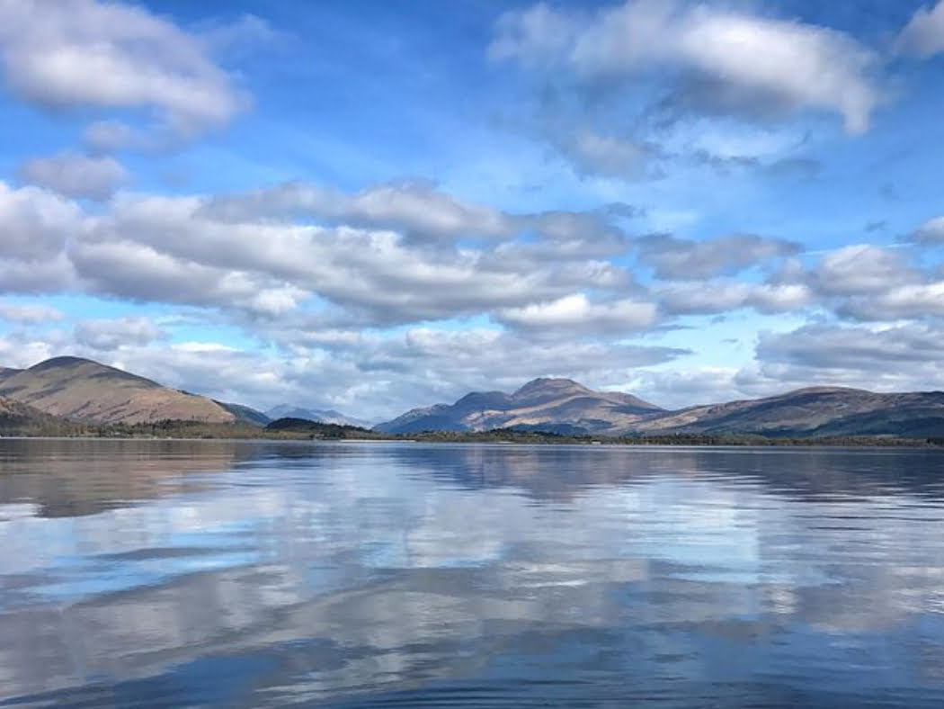 The lower half of this image is Loch Lomond on our Stirling Castle and Highland Cattle Tour. The far shore of the loch comprises the many mountains of the Highlands, blue and blue-green in colour. The sky is filled with clouds and is a mix of blue and white.