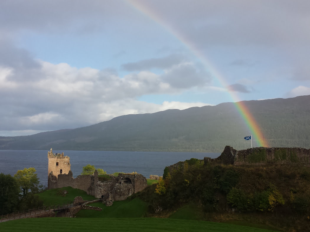 A ruined castle castle on a rock in a grey-blue lake. The tower at the left end is sunlit, but the rest of the ruins not. Except there is a vivid rainbow arcing straight down upon the Scottish flag flying at the castle highpoint.