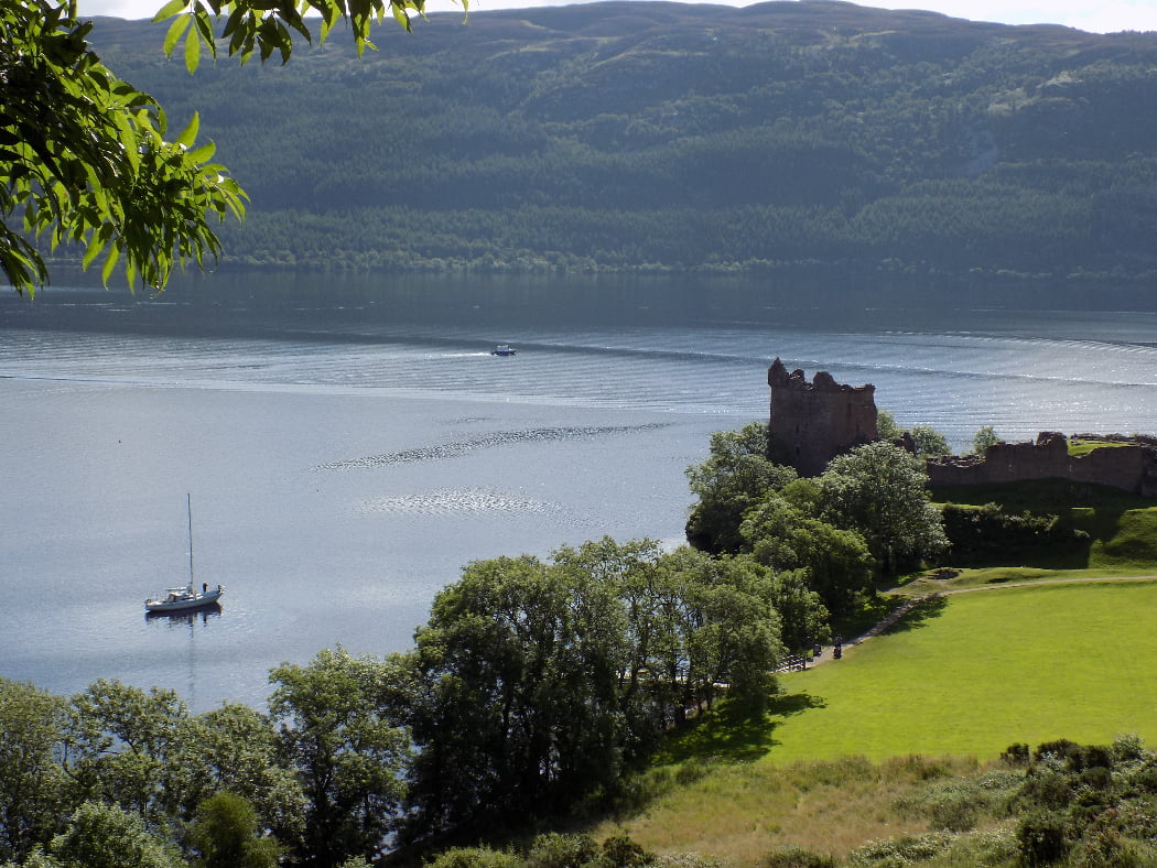 Wooded hills under a white sky in the background and a lake in front, on our Eilean Donan Castle Tour. A ruined castle overlooks the lake, upon which there is a sailboat and a small cabin cruiser. There are mature deciduous trees along the lake shore, and mown grass in the foreground in front of the castle.