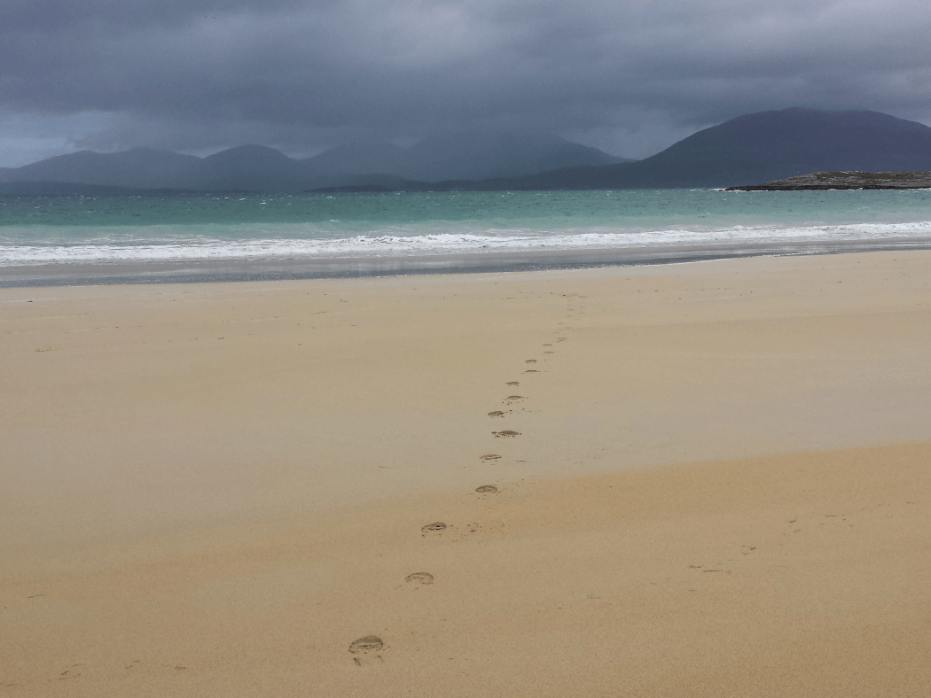 Footprints in the sand heading to ocean at Luskentyre on our Hebrides – Four Day Tour