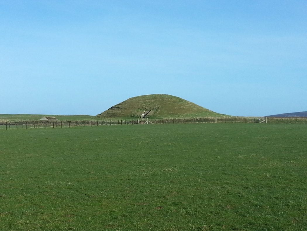 large photograph of the view across a grassy field to the small green hill that is Maeshowe Chambered Cairn on Orkney. Blue sky above