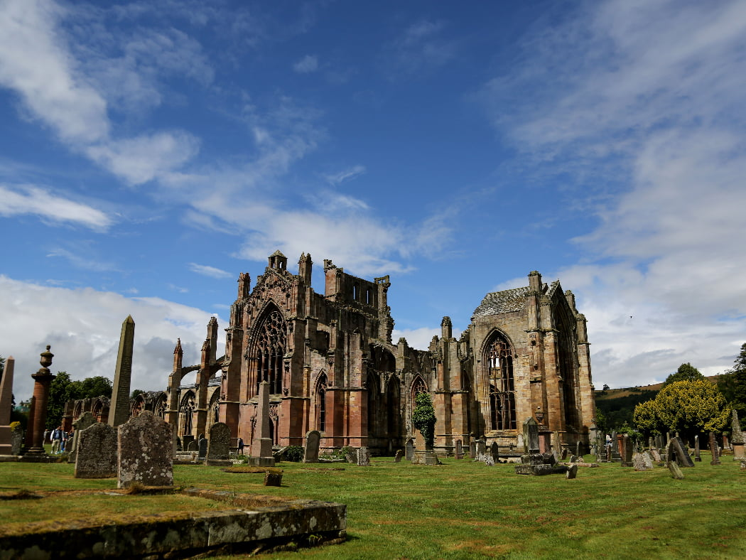 Ruined Melrose Abbey, visited on the Scottish Borders and Rosslyn Chapel Tour, is here under a mainly blue sky. Tombstones on green grass surround the ruin, and to the right, in the far distance rises a green hill.