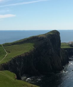 There is a large point of land covered with green grass and with high cliffs spearing out into the blue Atlantic Ocean. Neist Point Lighthouse, part of our Isle of Skye Three Day Tour, is right on the end of the peninsula. The sky is blue, and the lighthouse is white.