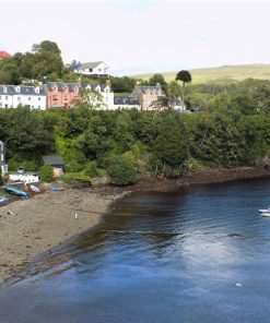 We look down from above to the blue water of Portree Bay. There are two very small dingies floating offshore. Half a dozen further dingies are pulled up on the shingle shoreline, and brightly coloured houses encircle the bay, amid trees.