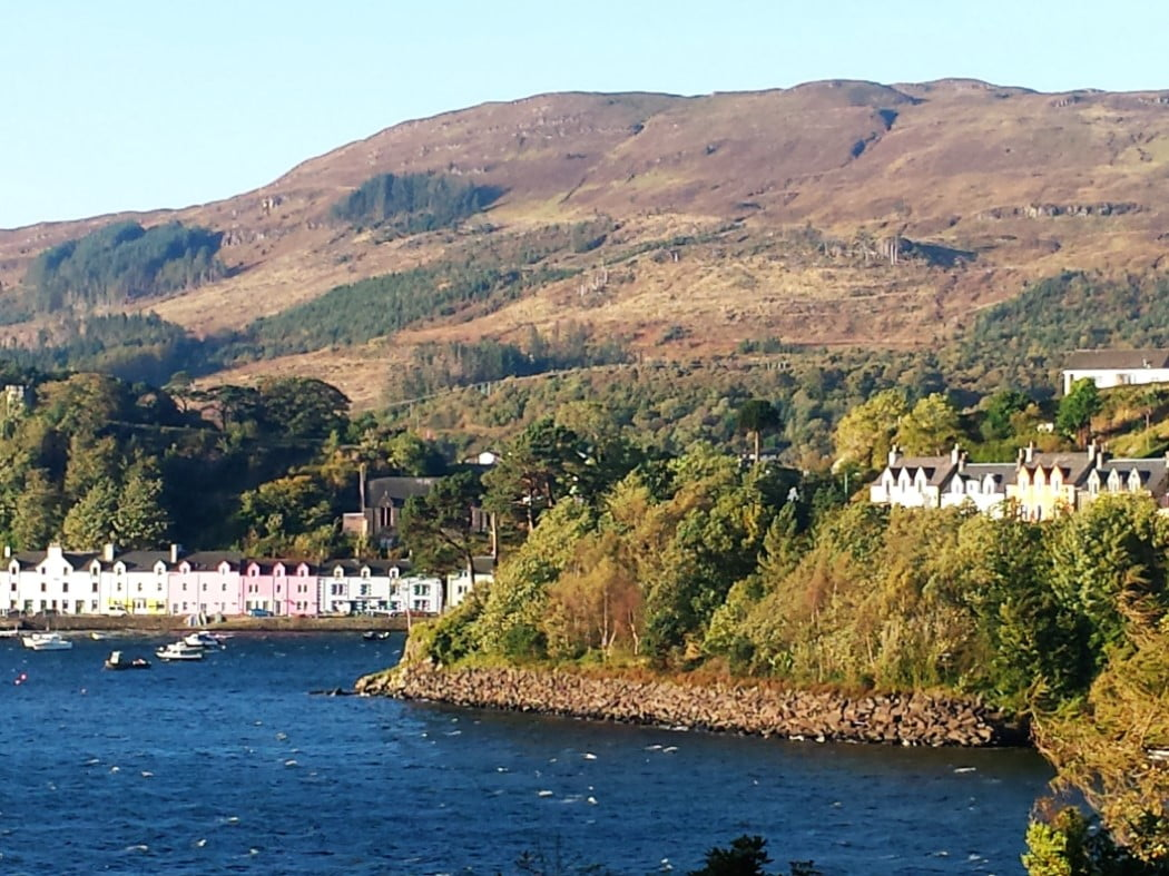 Two lines of brightly painted houses of different colours in Portree, on our Skye and Eilean Donan Castle Tour. One line is along the harbour side and the other is among the trees partway up the hill on the right of the picture, overlooking the harbour.