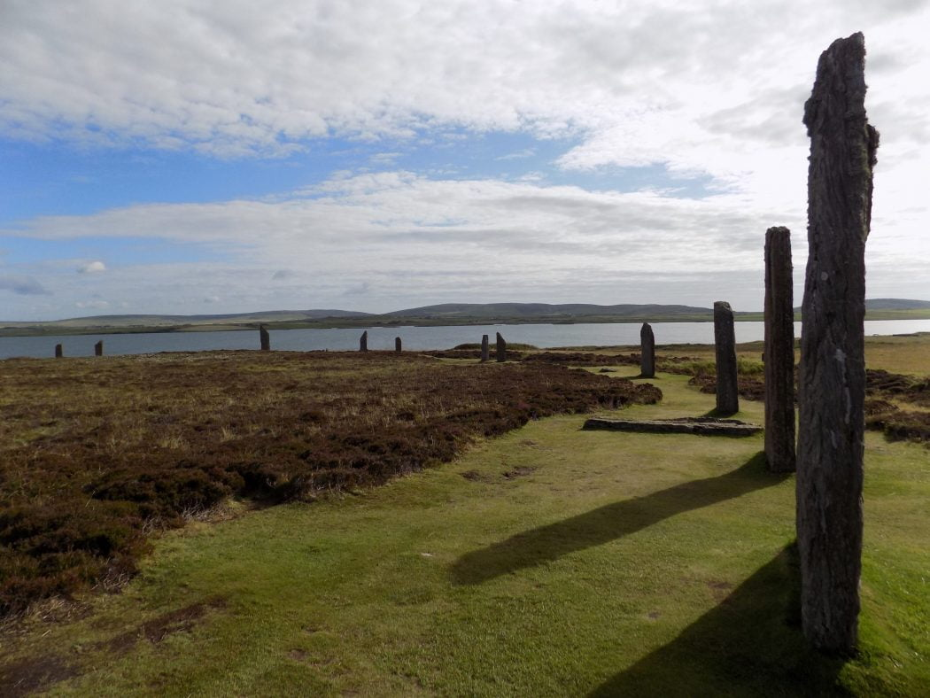 Curving line of standing stones on our Orkney - Two Day Tour. The Stones are arising from grass, but otherwise surrounded by heather. The sky above is cloudless blue and the Loch of Harray is in the background..
