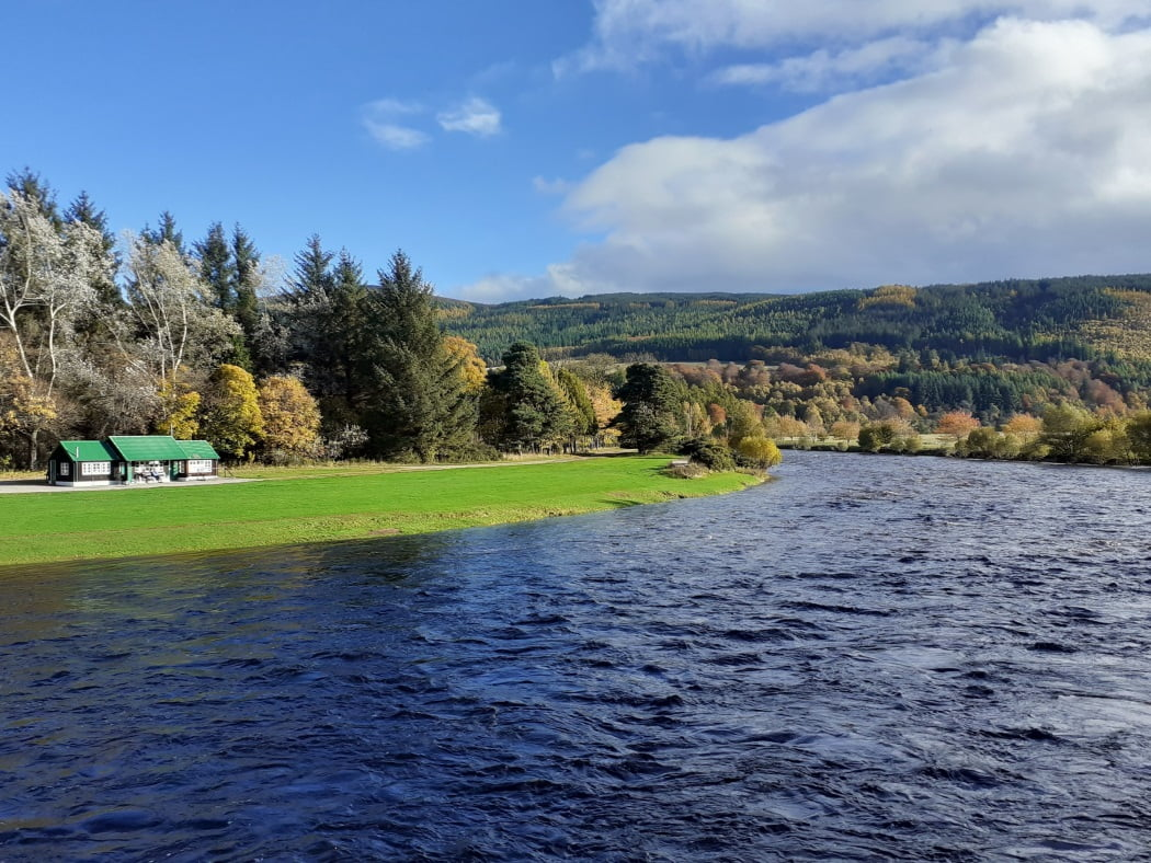 The River Spey is wide and powerful here, filling the picture, and flowing towards us in a deep blue colour. The far bank is mowed green grass with a salmon fly-fishing shelter. In the background rise forest covered hills under a blue sky with clouds to the right.