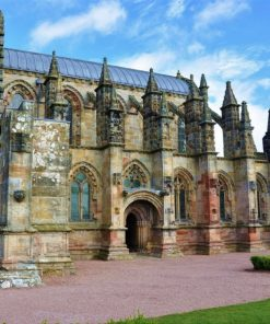 Under a blue and white-cloud sky stands 1400's Rosslyn Chapel. It is intricately carved and one of the best examples of Gothic architecture is Scotland.