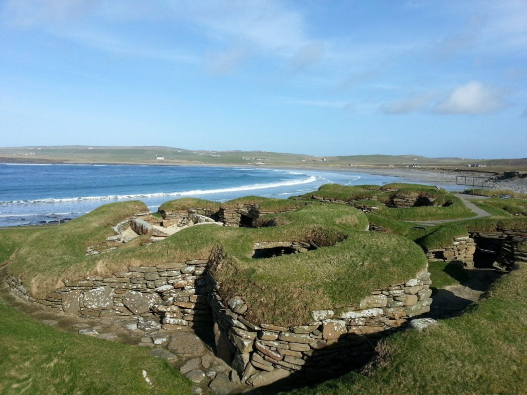 In the foreground are the low ruins of Skara Brae, Stone Age village, visited on our Orkney Tours. Behind this is the broad crescent of the Bay Of Skaill, with a lazy Atlantic swell coming in over the sand, under a blue sky.