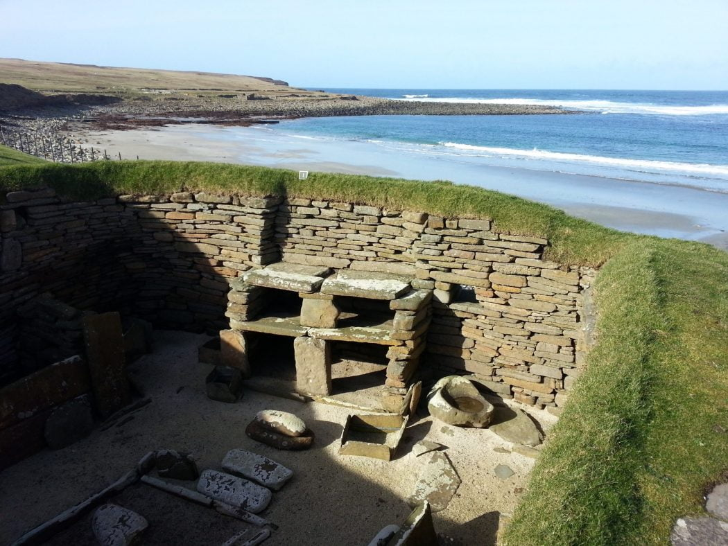 View inside a neolithic house in skara brae with ocean scenery behind, on our Orkney - Three Day Tour