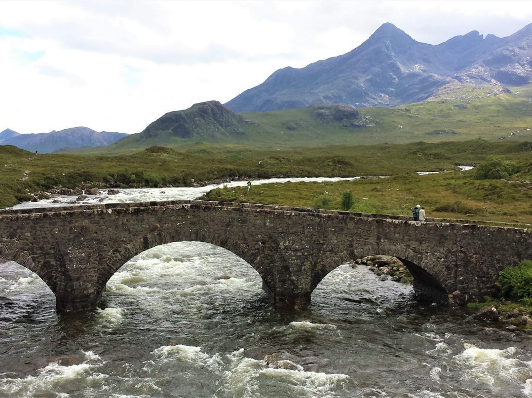 An old three-arched stone bridge crosses a river in spate on our Isle of Skye and Dunvegan Castle Tour. The river is flowing down from the Black Cuillin Mountains, more specifically from the tall black peak in the back right of the picture.