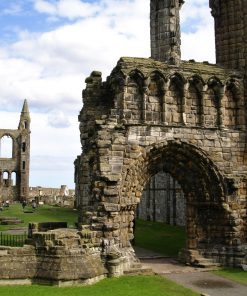 The fragmentary ruins of St Andrews Abbey are seen under a cloudy blue sky. There is a stone-arched gateway, then the mown grass which occupies what used to be the Abbey interior. At the far end we see two ruined pointed towers connected by a wall which has the large empty frame of a once magnificent window.
