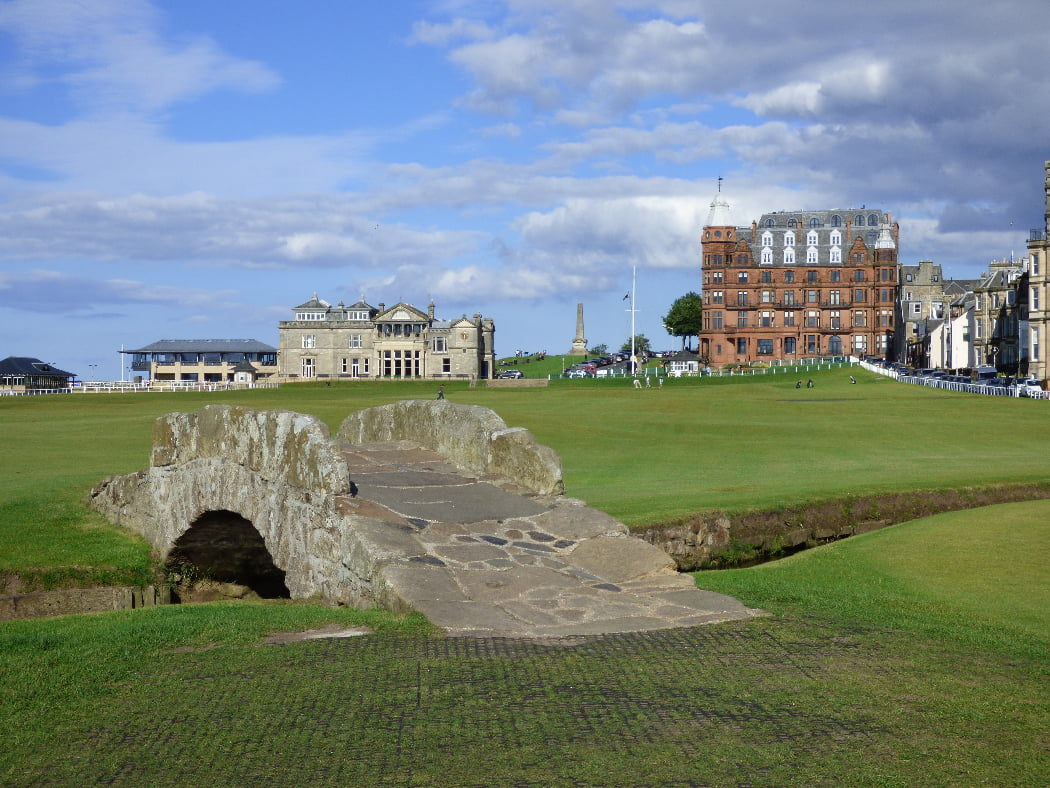 The foreground is dominated by the green of the golf course and a small old stone bridge across a ditch. The world famous Old Course golf clubhouse is central on the near horizon, and the buildings of the town are mid-right edge. Above is a cloudy blue sky.