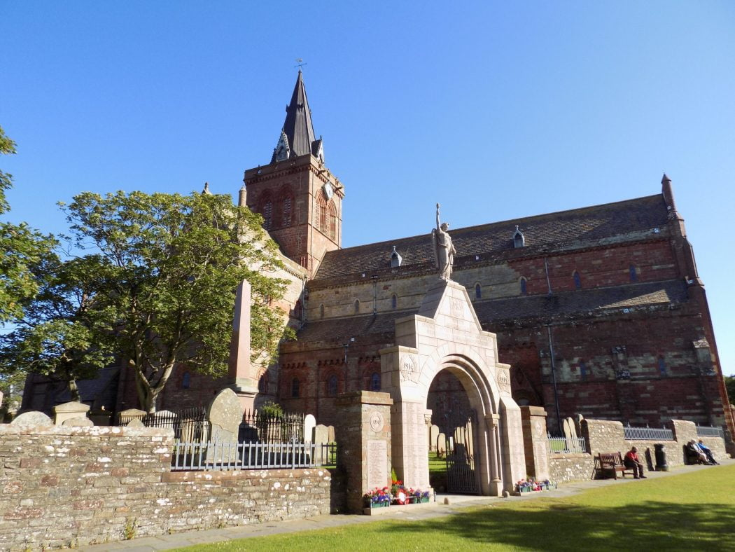 St Magnus Cathedral in Kirkwall on our Orkney – Two Day Tour. There is a stone archway into the graveyard in front of us, and the cathedral is behind that, under a cloudless blue sky.