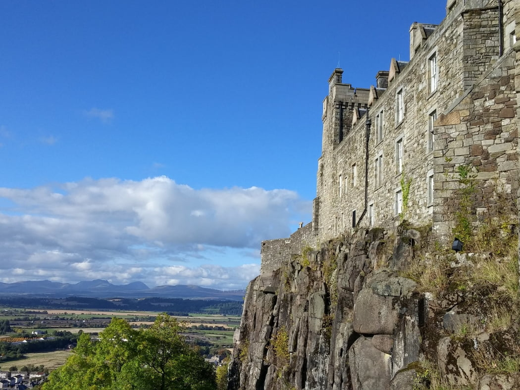 A close-up view of Stirling Castle, on our Wallace Monument Tour fills the right side of the image. The castle is above the line of sight, and the cliff falls from our location. The day is fine and across the flat green fields below us, we can see the blue mountains of the Highlands on the far horizon.