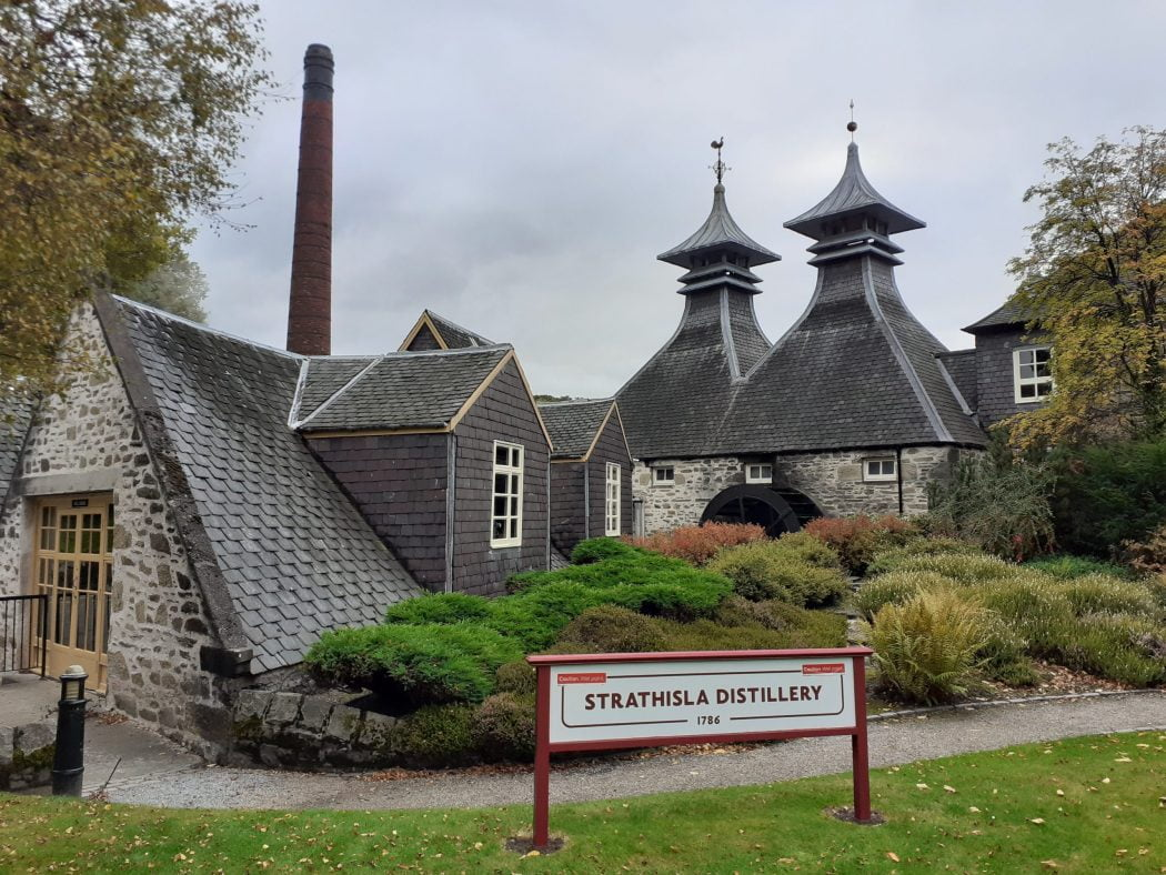 1700's Strathisla Distillery on our Moray Coast and Speyside Tour. In the foreground the wide distillery sign stands on grass, and behind is a tall chimney, two pagoda roofed drying rooms and a water wheel. There are trees in autumn colours to left and right and the sky is grey.