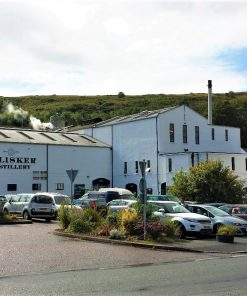 In the foreground is a full car park. The large white painted building occupying the whole of the middle-distance says Talisker Distillery on it. In the background a green hill rises towards a mixed blue and cloudy sky.