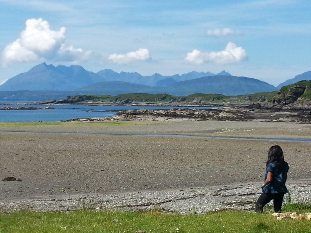 Looking toward the jagged peaks of the Black Cuillin Mountains from Tarskavaig Bay. A shingle beach stretches down to the blue sea. The mountains are a slightly darker blue and the sky slightly lighter.