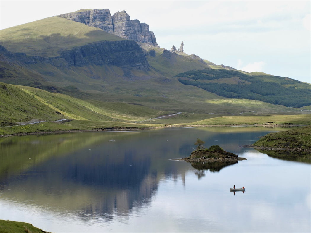 There is a large fractured pyramidal mountain in the background and a large finger or pinnacle of rock to its right. These are famous features of the Isle of Skye and Trotternish Peninsula Tour. The foreground is a freshwater lake with a small island sporting one single tree. There are two rowboats each containing a standing fly fisherman.