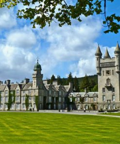 Balmoral Castle fills this picture. There are green lawns in front of the castle and the Royal Standard flies from the highest tower. There are forested hills behind, and a cloudy and blue sky above.