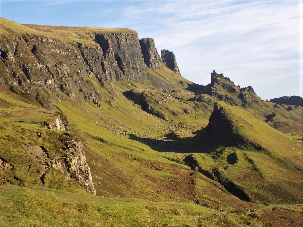 This picture is of a major landslip viewed on our Isle of Skye and Trotternish Peninsula Tour. The sky above is blue and the grass in the foreground is green, but overwhelmingly the great cliffs are black and shattered into cracks, chasms and pinnacles.