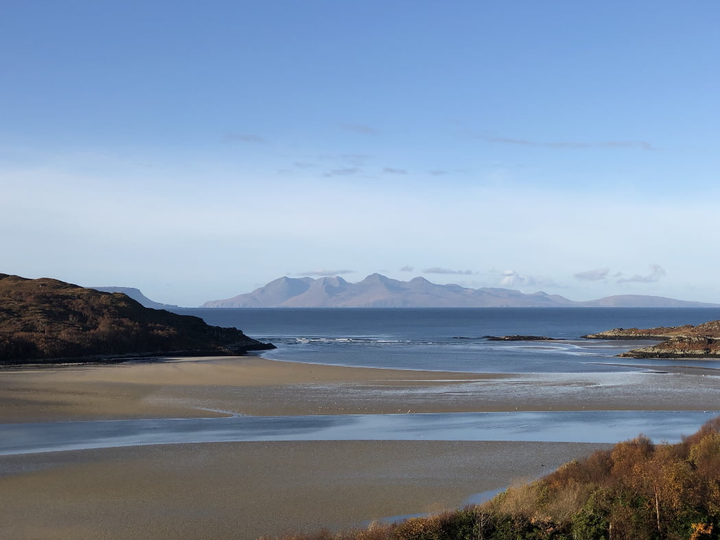 Sandy beach with wooded headlands to right and left. The blue sea is in the background and blue peaked islands lie out on the horizon under a blue sky.