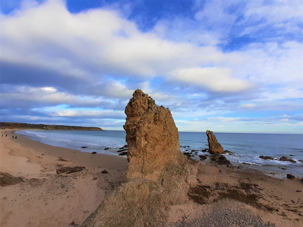 Two red coloured rock pinnacles rising from a sandy beach. The ocean is behind them and the sky is a mix of cloud and blue.