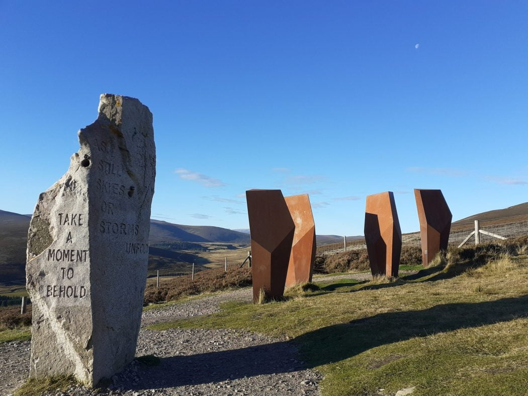 Five modern Standing Stones, four of which are geometric. They stand in grass and gravel on a hillside above a valley. The sky is blue, and a winter moon hangs above this art installation.