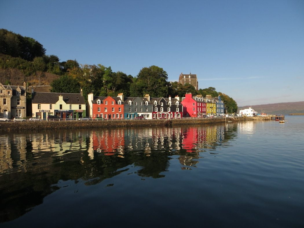The brightly coloured houses of Tobermory are prettily reflected in the harbour waters beneath a blue sky during the isle of Mull and Duart Castle Tour. Behind the houses are deciduous trees.