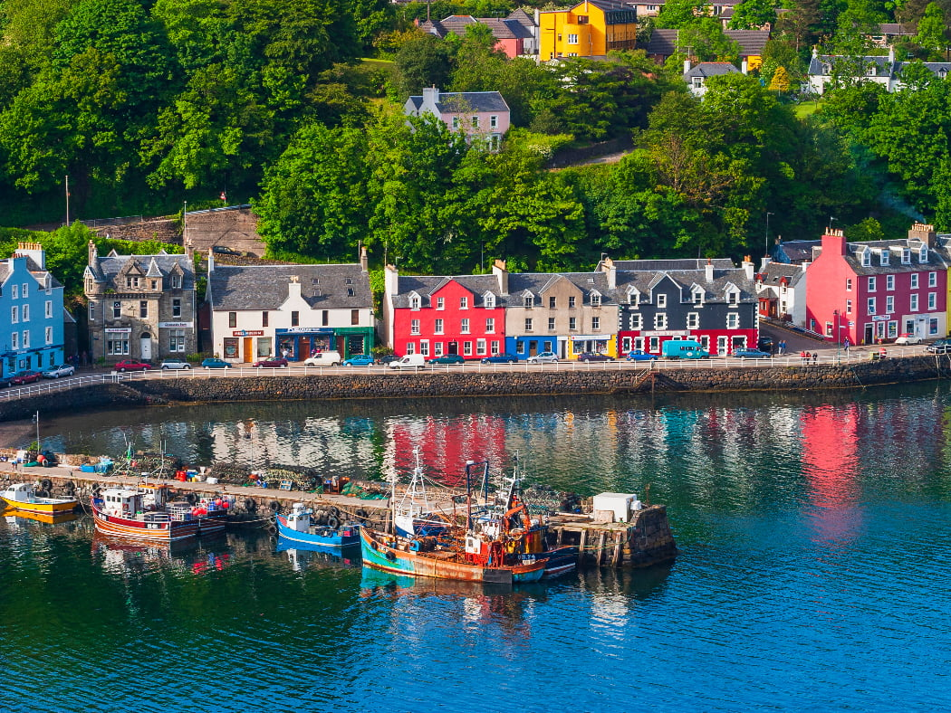 Arial view of Tobermory on our Isle of Skye and Mull Tour. Colourful houses line the harbourfront and a stone built pier projects into a calm blue sea. Six colourful fishing boats are tied to the pier.