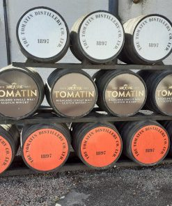 A rack of barrels at Tomatin Distillery on the West Coast and Highland Distillery Tour. The barrels are on their sides and the bottom level has 5 Tomatin barrels showing orange ends. The next level up has four brown-ended Tomatin barrels, and the top deck has three white-ended Tomatin barrels.