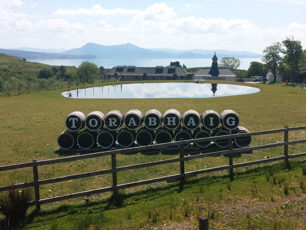 In the background are the faded blue mountains of the mainland and in the foreground is the new distillery, Torobhaig. We sometimes visit it on the Isle of Skye and Hogwarts Express Tour. It is a long low building above the sea, and it is reflected in a pond on the grass in front of us. Closest to us is a line of barrels. Each has a letter painted on it, spelling out the name Torabhaig.