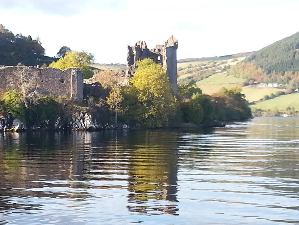 A ruined castle rises on a wooded outcrop from the waters of a lake. Our viewpoint is from a boat offshore. In the background, behind the castle rises a hill with farms and farmland upon it. The sky is white.