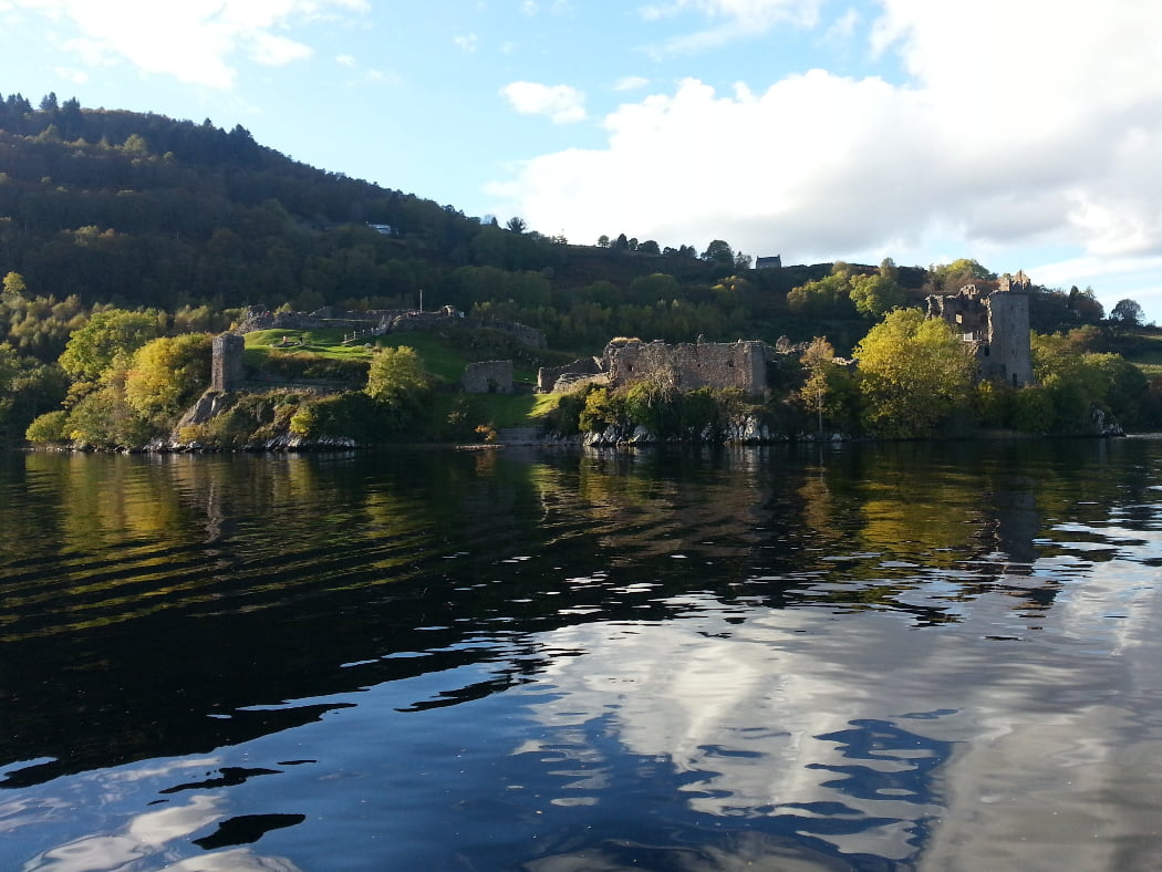 The lower half of the image taken on the Loch Ness with Culloden and Urquhart Castle Tour is filled with the dark calm waters of a lake. Just above the mid-line is a rocky promontery with a very ruined castle, grass and bushes. Behind rises a tree-covered hill (higher towards the left. Above is a sky of mixed blue and cloud.