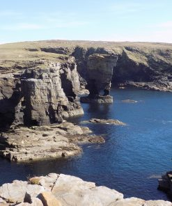 wide image of the sunny cliff scenery and rock formations known as Yesnaby Castle sea stack on Orkney. Avery light blue sky, and deep blue sea.