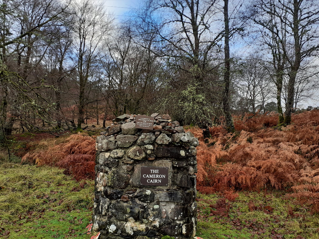 Front and centre is a mortared cairn comprising grey and black stones, about four feet tall. On it's front is fixed a plaques with white lettering on dark background, sating The Cameron Cairn. The ground is grass, the backdrop is russet dead bracken-ferns and leafless winter trees, and the sky is blue.