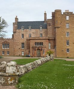 A red stone built castle of obviously differing ages. The 5 storey old keep with pepper-pot towers and flatter roof is at the right hand end. The middle section is 4 storeys and slate roofed, and the left hand end is two storeys and embattled. There are lawns with gravel drive in front, and a low wall running straight out of the picture towards us.