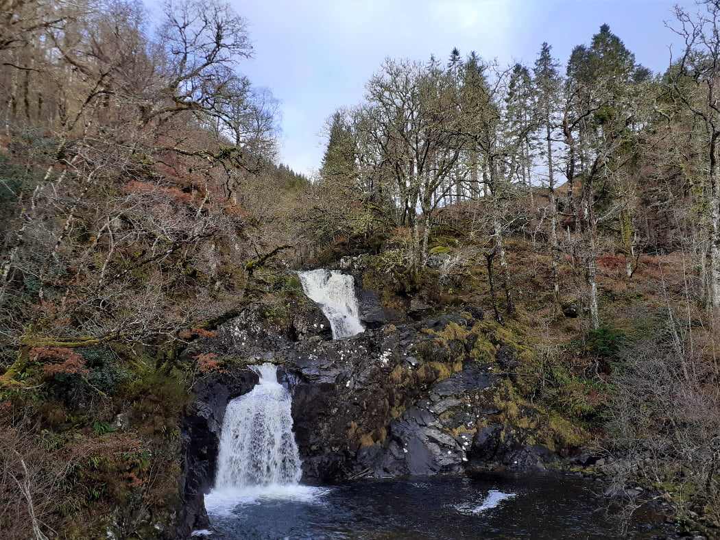 The Cia-aig Falls on our Clan Cameron Tour from Inverness are front and centre here. They cascade down, in two main falls, together being nearly 60 feet. The sky above is blue, the water very white, and the rocks overwhelmingly black. The banks are steep and clothed in leafless, winter deciduous trees.