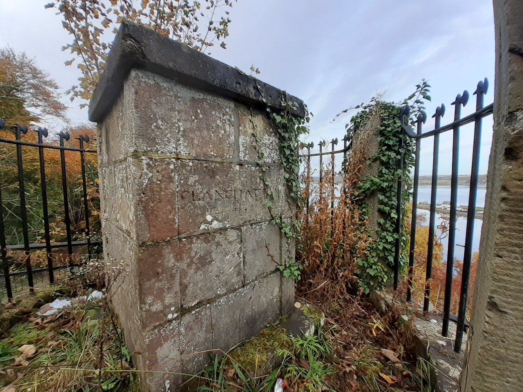 The bulk of the picture is a square grey flat-topped stone monument (about 4 feet high) with some ivy strands. The words CLANCHATT are unobscured by ivy. It can be assumed that AN are the letters below the vegetation. Iron railings surround the site, and through them to the right we can see down to a sea inlet and green hills on the far side in the distance. A blue sky above.