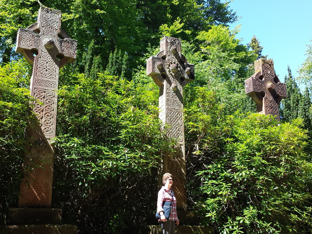 These are the three huge Celtic Crosses (clearly over 12 feet tall) in the Clan Chisholm graveyard on our tour from Inverness. There is a person standing at the base of the middle cross which puts size in perspective. The sun is shining, the sky is white, and there is a lot of undergrowth behind the crosses (Rhododendrons and trees).