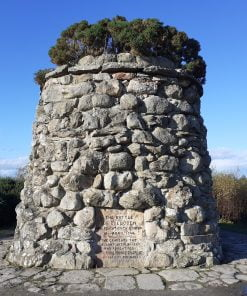 A large monument with bushes on the top stands 20 feet tall under a vivid blue sky on an open moor on our Loch Ness with Culloden and Urquhart Castle Tour