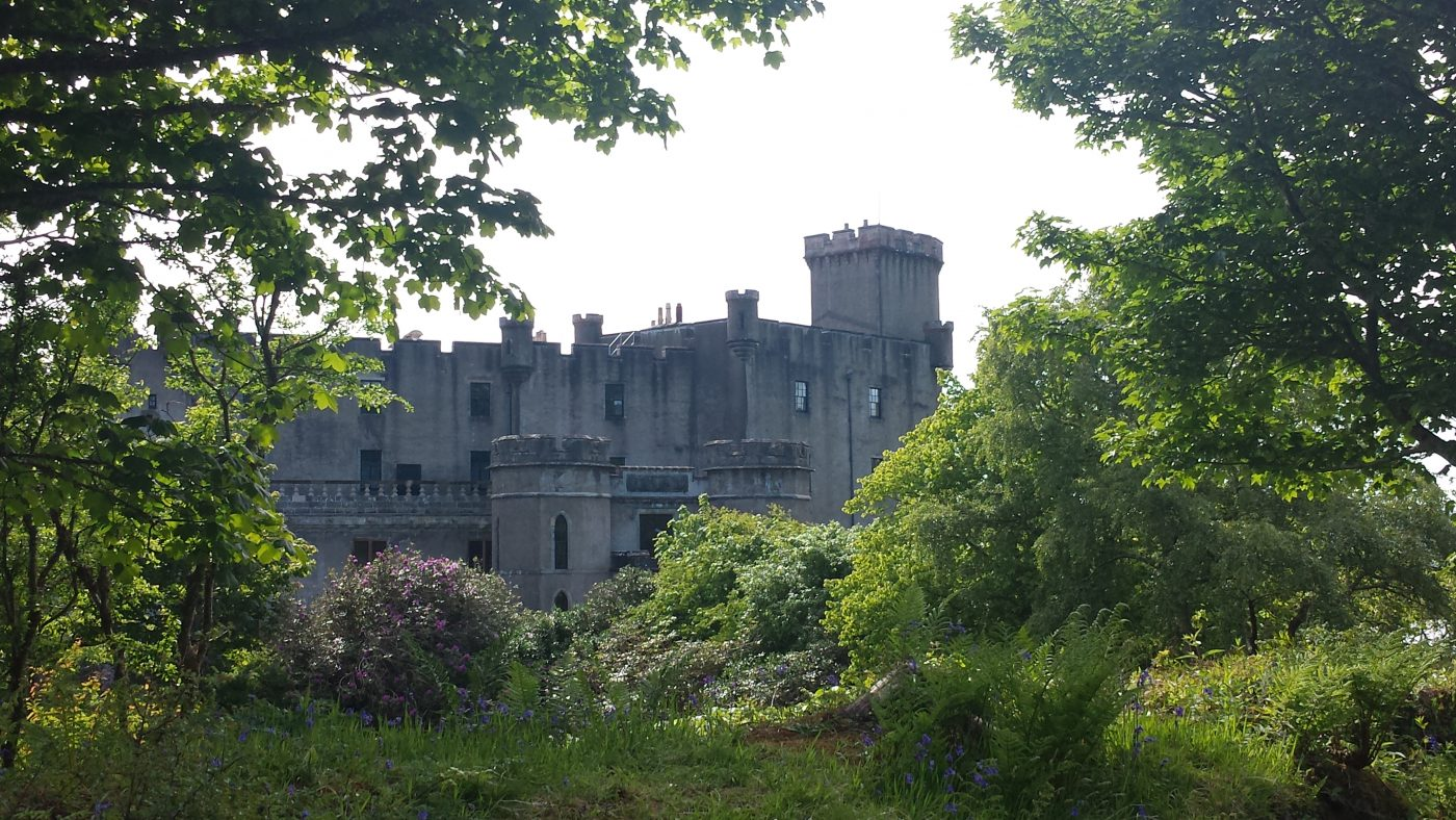 The grey harling towers of Dunvegan Castle are central in this picture. But the picture is taken from the gardens, and so the castle view is completely framed in bushes, flowers and trees.