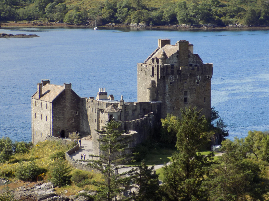 A castle, viewed from above, almost fills this image. It is Scottish Atlantic Seaboard design dating originally from 1200s. Behind is a blue arm of the sea, and a wooded far shore.